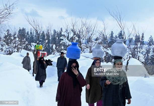 Villagers carry water pots after a heavy snowfall at Kanidajan area of Budgam district in Srinagar on January 18 2020
