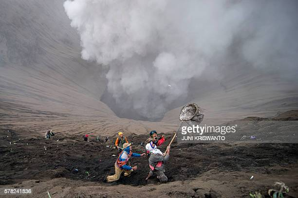 TOPSHOT Villagers catch coin offerings released by Hindu devotees of the Tengger tribe during the Yadnya Kasada festival on the crater of Mount Bromo...