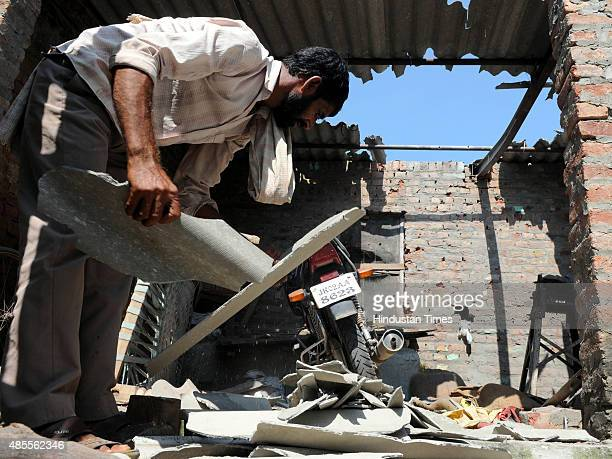 Villagers clearing the damaged shed after mortar shell fired by Pakistan rangers at Sai village in Abdullia sector about 55 km from Jammu on Friday...