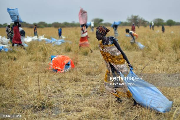 Villagers collect food aid dropped from a plane in gunny bags from a plane onto a drop zone at a village in Ayod county South Sudan where World Food...