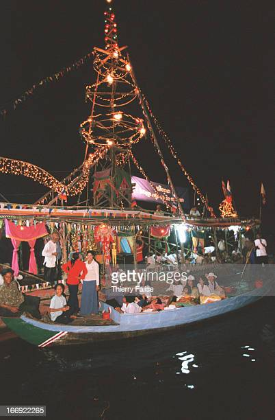 Villagers come to get blessed by Buddhist monks on an illuminated boat during the water festival at the Tonle Sap or Great Lake of Cambodia