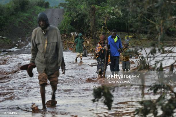 TOPSHOT Villagers cross through receding waters in an area of flash flooding at Solai in Subukia Nakuru County on May 10 after the banks of a private...
