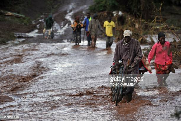 Villagers cross through receding waters in an area of flash flooding at Solai in Subukia Nakuru County on May 10 after the banks of a private dam...