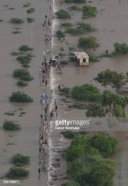 Villagers displaced by floods travel through flood waters on August 29 2010 near Thatta near Hyderabad in Sindh province Pakistan The country's...