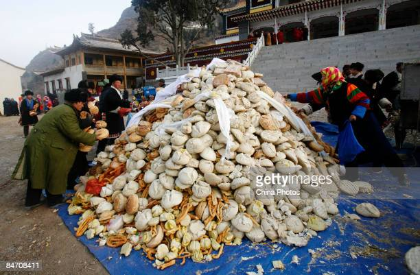 Villagers donate their bread to lamas as offerings during the 'Tiaoqian' praying ceremony at the Youning Temple on February 8 2009 in Huzhu County of...
