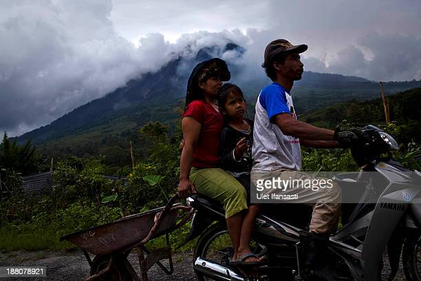 Villagers drive a motorcycle past mount Sinabung spewing ash in the background in Kuta Tonggal village on November 15 2013 in Karo district South...
