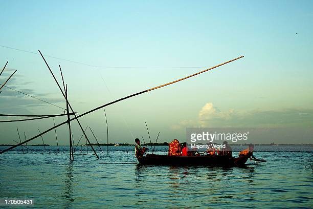 Villagers enjoy riding boat in the Padma River Bangladesh August 9 2007