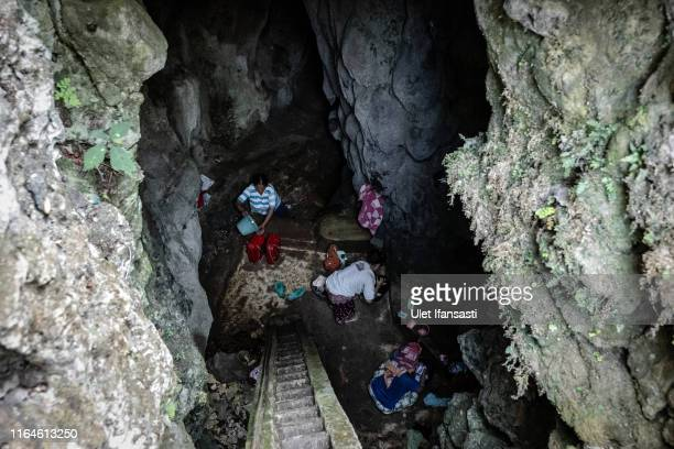 Villagers fill buckets full of water inside a cave at Klepu village Sawahan Kulon on August 28 2019 in Pacitan East Java province Indonesia During...