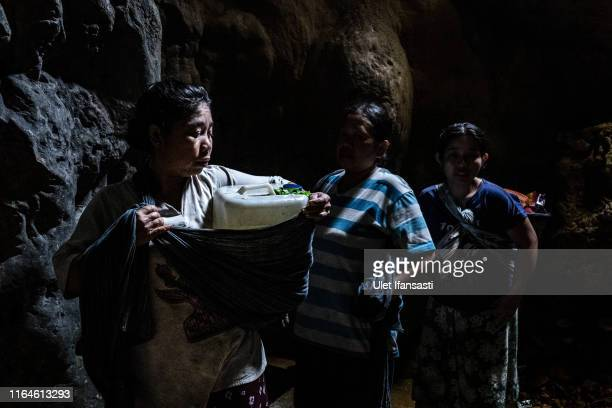 Villagers fill jerrycans full of water inside a cave at Klepu village Sawahan Kulon on August 28 2019 in Pacitan East Java province Indonesia During...