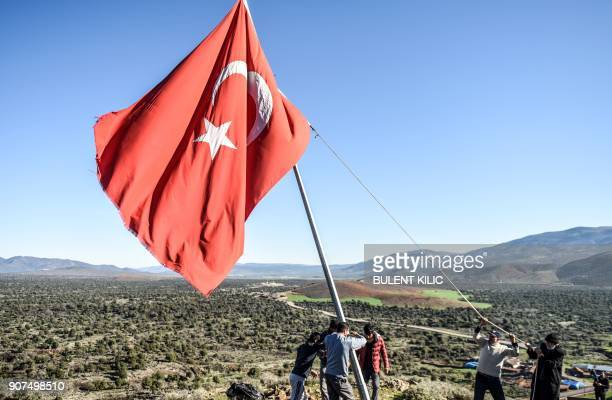 TOPSHOT Villagers fix a broken flagpole at Sugedik village Hatay province near the Syrian border on January 20 2018 / AFP PHOTO / BULENT KILIC