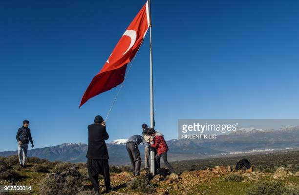 Villagers fix a broken Turkish flagpole near Syria border at Sugedik village Hatay province near the Syrian border on January 20 2018 / AFP PHOTO /...