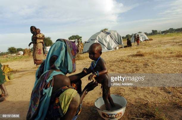 Villagers from Jameisi Jadida and other nearby recently attacked by Chadian Arabs linger at dawn in a makeshift camp for internally displaced persons...