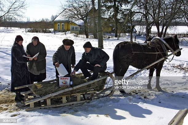 Villagers from Rytino village, some 70 kilometers west of Smolensk cast their vote for the Russian Presidential elections at a ballot box brought on...