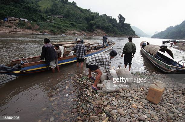 Villagers from the town of Muang Khua in northern Laos load sacks of grain and jerry cans onto a boat for the journey down the Nam Ou River to Muang...