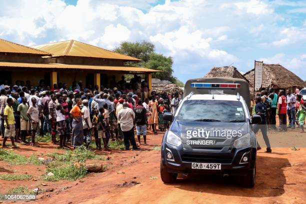 Villagers gather beside a police vehicle as they look at an area where a grenade exploded during an attack by a gang in Chakama village of the...