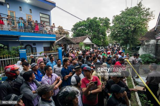 Villagers gather in front of a house under police investigation in the city of Bangil East Java province on July 5 after an alleged terrorist who...