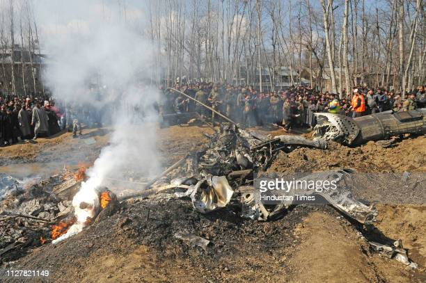 Villagers gather near the wreckage of an Indian Air Force helicopter after it crashed on February 27 2019 in Budgam India Two pilots were killed on...