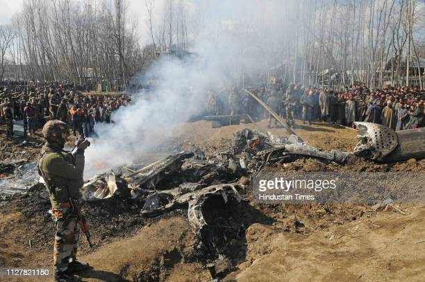 Villagers gather near the wreckage of an Indian Air Force helicopter after it crashed on February 27, 2019 in Budgam, India. Two pilots were killed...