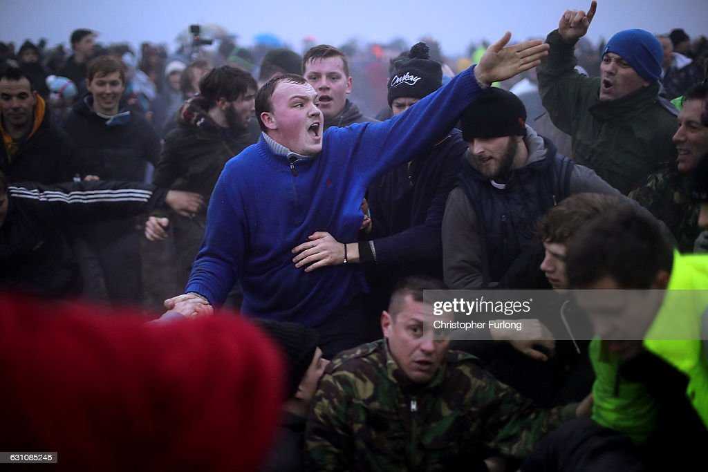 Villagers get caught in the sway (scrum) as they battle for the Haxey Hood at Haxey Village on January 6, 2017 in Doncaster, England. The origins of the ancient game of Haxey Hood goes back hundreds of years to the 14th century. Lady de Mowbray was out riding towards Westwoodside on the hill that separates it from the village of Haxey, when her silk riding hood was blown away by the wind, farm workers in the field rushed to help and chased the hood eventually it was caught by one of the men, but being too shy to hand it back to the lady, he gave it to one of the others to hand back to her. She thanked the farm worker who had returned the hood and said that he had acted like a Lord, whereas the worker who had actually caught the hood was a Fool. The act of chivalry and the resulting chase amused her so much she donated 13 acres of land on condition that the chase for the hood would be re-enacted each year.