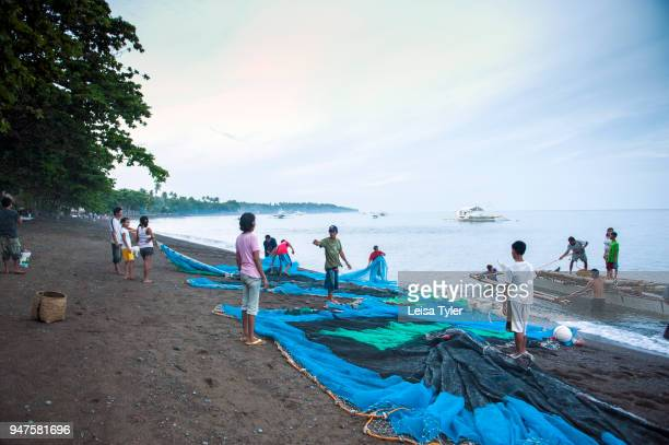 Villagers hauling in fishing nets on Dauin Beach, south of Dumaguete City in Negros Oriental.