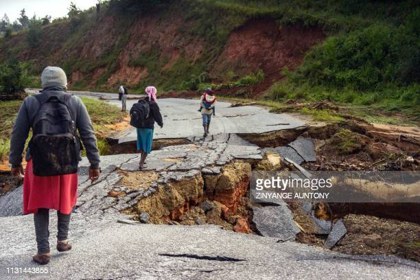 Villagers heading to Chimanimani on foot cross a damaged road in the morning of March 18 2019 near Chimanimani eastern Zimbabwe after the area was...