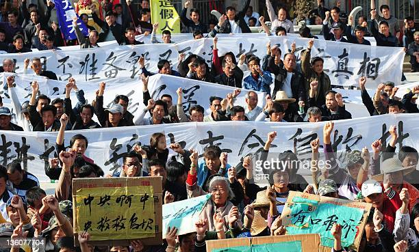 Villagers hold banners during a protest rally by residents of Wukan a fishing village in the southern province of Guangdong as they demand the...
