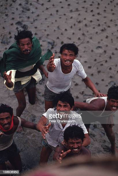 Villagers in a remote region of Bangladesh reach up for food being dropped from a helicopter bringing food and emergency supplies to those in need...