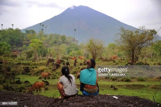 TOPSHOT Villagers look at the Mount Agung volcano from Kubu subdistrict in Karangasem Regency on Indonesia's resort island of Bali on December 3 2017...
