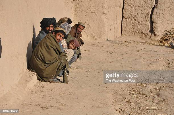 Villagers look by as British forces patrol the fields in Khar Nikah in Nahre Saraj district Helmand province Afghanistan on January 3 2012