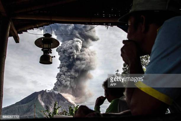 TOPSHOT Villagers look on as Mount Sinabung volcano spews thick volcanic ash as seen from Beganding village in Karo North Sumatra province on May 19...