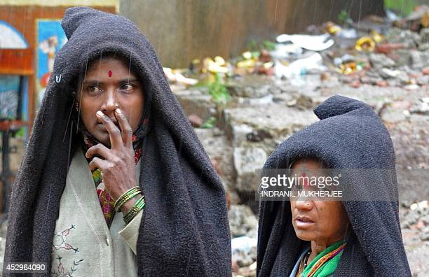 Villagers look on as rescue work continues at the scene of the landslide in Malin village in Pune district of India's western state of Maharashtra on...