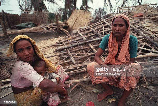Villagers look shellshocked as they sit by the devastated remains of their village All the houses in this village near the mouth of a river were...