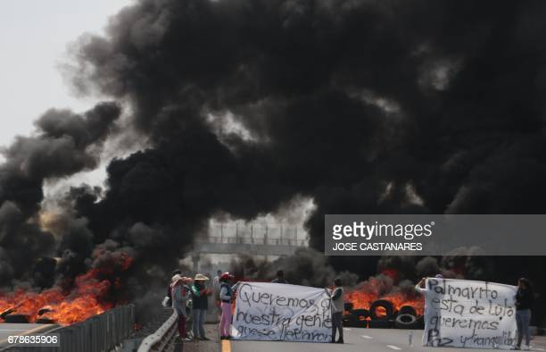 Villagers mount roadblocks with burning tires to protest an army crackdown the day after a clash between soldiers and alleged fuel thieves known as...