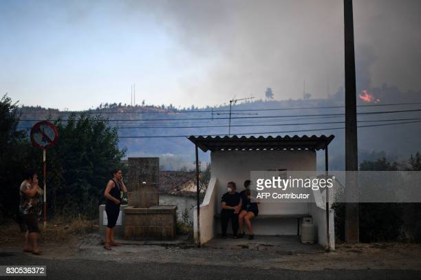 Villagers of Rio de Moinhos stand at a bus stop wearing masks following a new rash of forest fires ahead of a weekend of warm temperatures at Rio de...
