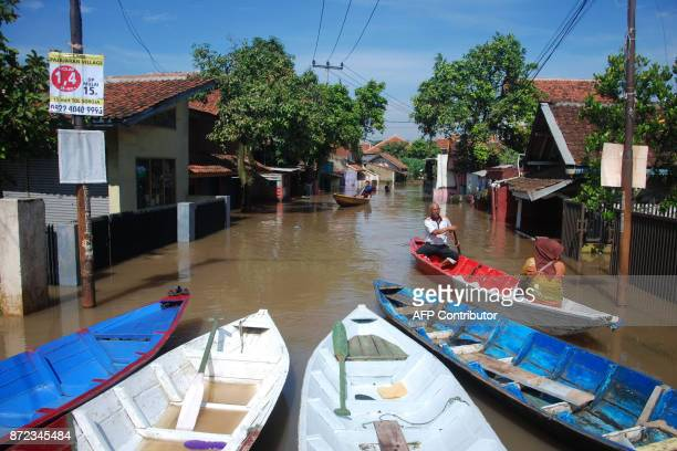 Villagers park their wooden boats along a flooded road in Bale Endah village in Bandung West Java on November 10 2017 Landslides and flooding are...
