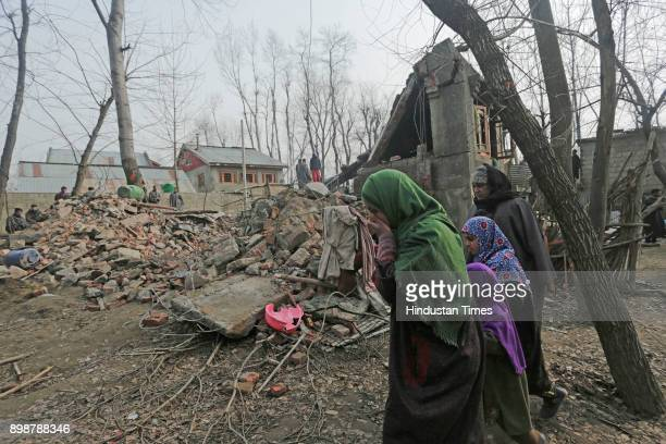 Villagers pass by the debris of a residential house which was destroyed during a gunfight at Samboora on December 26 2017 in Pulwama some 30...