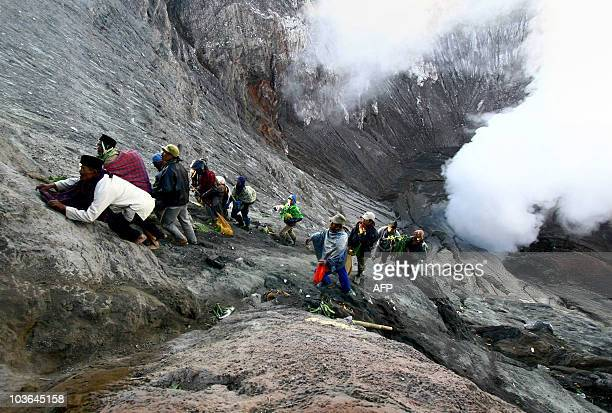 Villagers perched on the crater of Mount Bromo in East Java catch offerings thrown by Indonesian Hindu pilgrims to the smouldering crater on August...