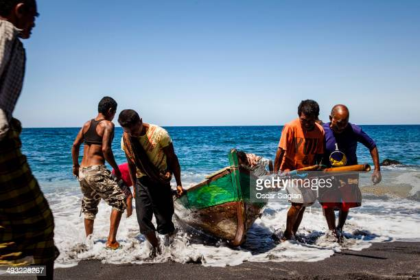Villagers pull their boat ashore on May 2 2014 in Lamalera village East Nusa Tenggara Indonesia The remote indigenous villagers use ancient hunting...
