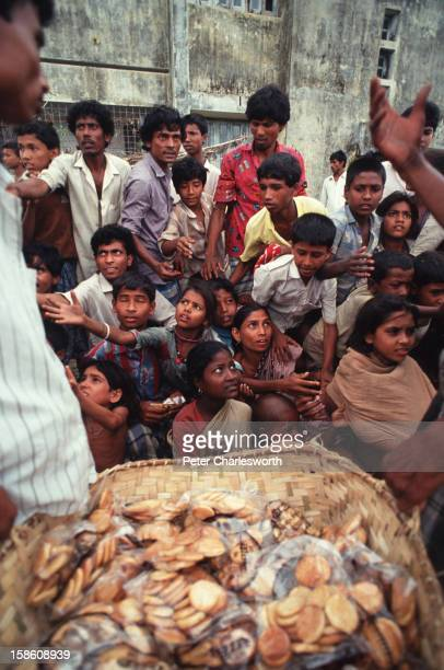 Villagers queue for emergency relief packages of biscuits that have arrived on an army helicopter These young people have just survived one of the...