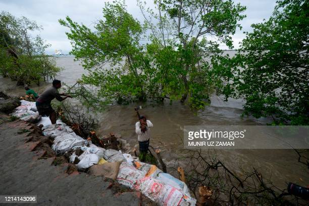 Villagers reinforce an embankment with sacks of soil ahead of the expected landfall of cyclone Amphan in Dacope on May 20 2020 Several million people...