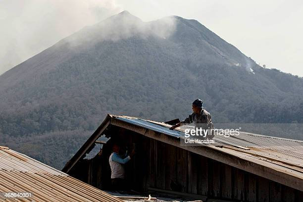 Villagers repair a house roof damaged by the eruptions of Mount Sinabung as Mount Sinabung spews ash at Kuta Gugung village on February 11 2014 in...