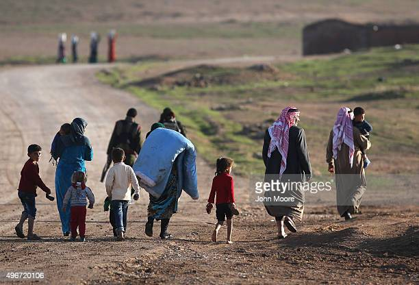 Villagers return home after troops from the Syrian Democratic Forces, a coalition of Kurdish and Arab forces, retook a town on November 11, 2015 near...