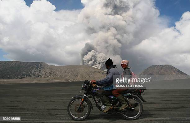 TOPSHOT Villagers ride a motorbike past smoke and ash rising from the eruption of Mount Bromo in Probolinggo in eastern Java island on December 12...