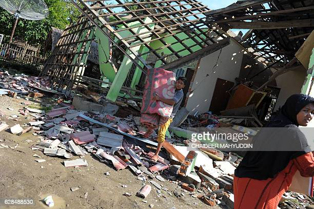Villagers salvage goods from their house which was damaged in an earthquake in Kuta Pangwa village in Pidie Jaya on December 8 2016 Every house in...
