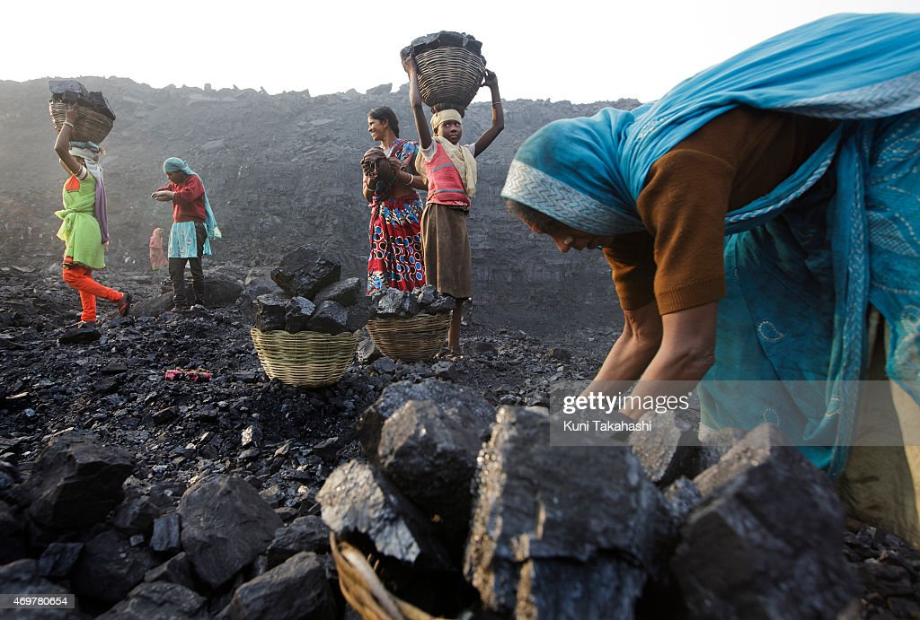 Villagers scavenge coal from an open-cast coal mine in Dhanbad, Jharkhand, India on December 6, 2014, trying to earn a few dollars a day. Indian government lead by Prime Minister Narendra Modi plans to double its coal production by 2019.