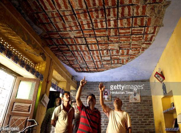 Villagers show the damaged roof of their house after a heavy mortar shelling by Pakistan Rangers on Saturday night at Arnia village on September 17...