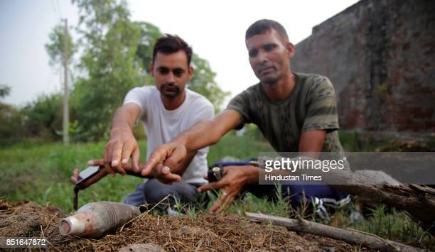 Villagers showing a live mortar shell fired from the Pakistan side of the border at Jabowal village in Arnia sector near the IndiaPakistan...