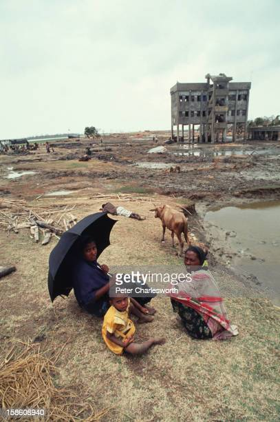 Villagers sit by the side of an all but destroyed dirt road with their stormravished farmlands a muddy wastland all around They have just survived...