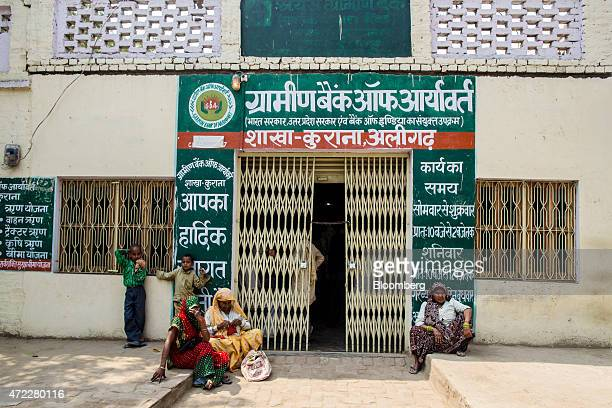 Villagers sit outside a branch of Gramin Bank of Aryavat sponsored by Bank of India in the village of Khurana Uttar Pradesh India on Monday April 13...