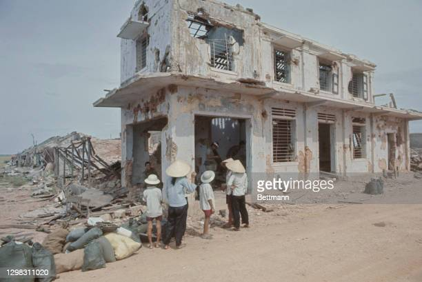 Villagers, some wearing a traditional non la hats, look on as South Vietnamese troops search a bombed-out building along Highway 555 some four...